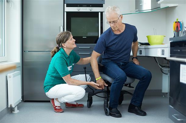 Bilde av ergoterapeut og mannlig pasient som tilpasser hjelpemidler på treningskjøkkenet