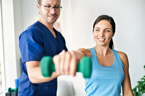 Mannlig fysioterapeut hjelper dame som løfter en manual
