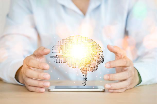 To hender holder illustrasjon av en hjerne over en iphone på et bord