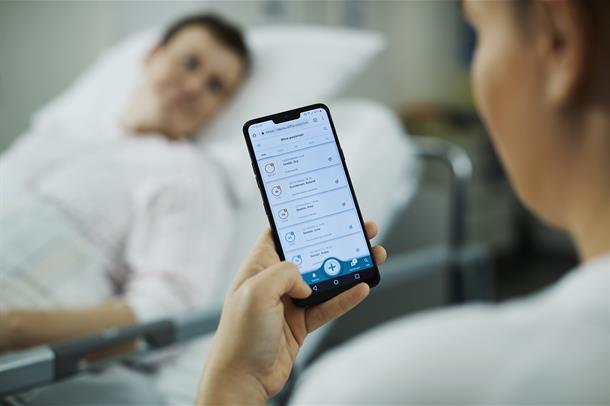 Kliniker holder mobiltelefon i hånden ved pasientseng