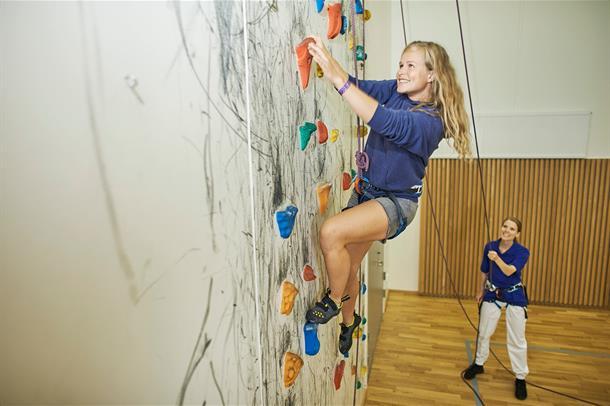 Bilde av en ung pasient som klatrer i klatreveggen på sykehuset. Hun bli sikret av en fysioterapeut.
