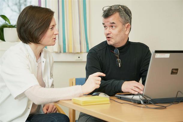 Pasient foran pc snakker med pedagog