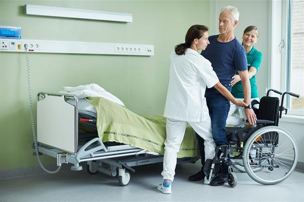 Sykepleier og ergoterapeut hjelper mannlig pasient fra rullestol og over i seng