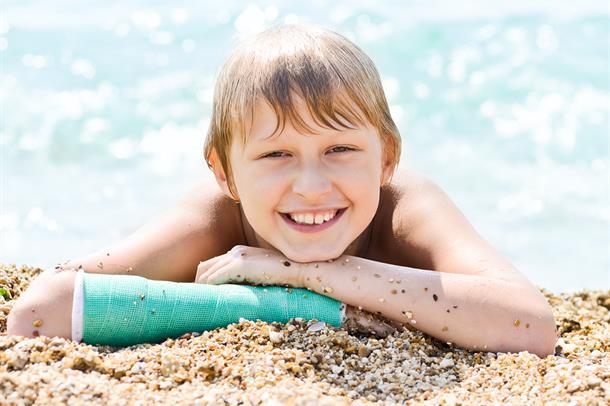 Illustarsjonsbilde av en gutt med armen i gips, på stranden