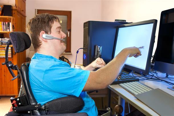 Mann i rullestol som jobber på pc